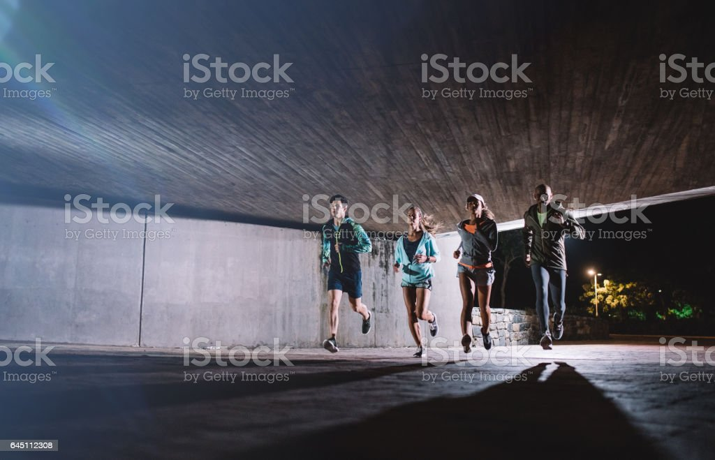Group of young people running together at night stock photo