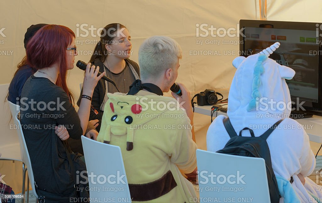 Group of young people singing at karaoke tent  at Animefest stock photo