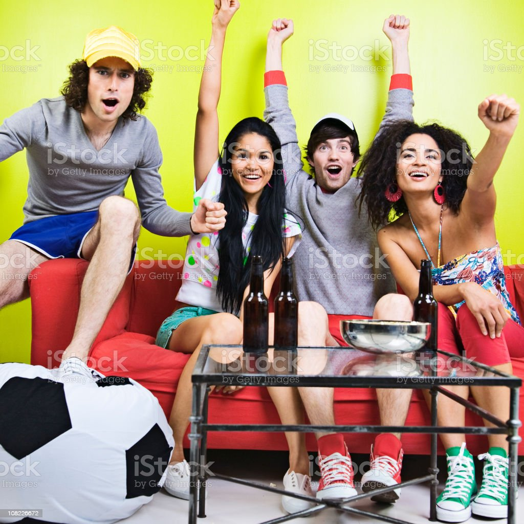 Group of Young People Sitting and Cheering on Couch royalty-free stock photo