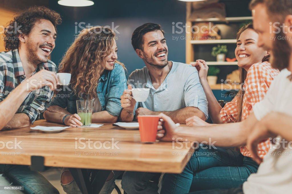 Grupo de jóvenes sentados y hablando en la cafetería - foto de stock