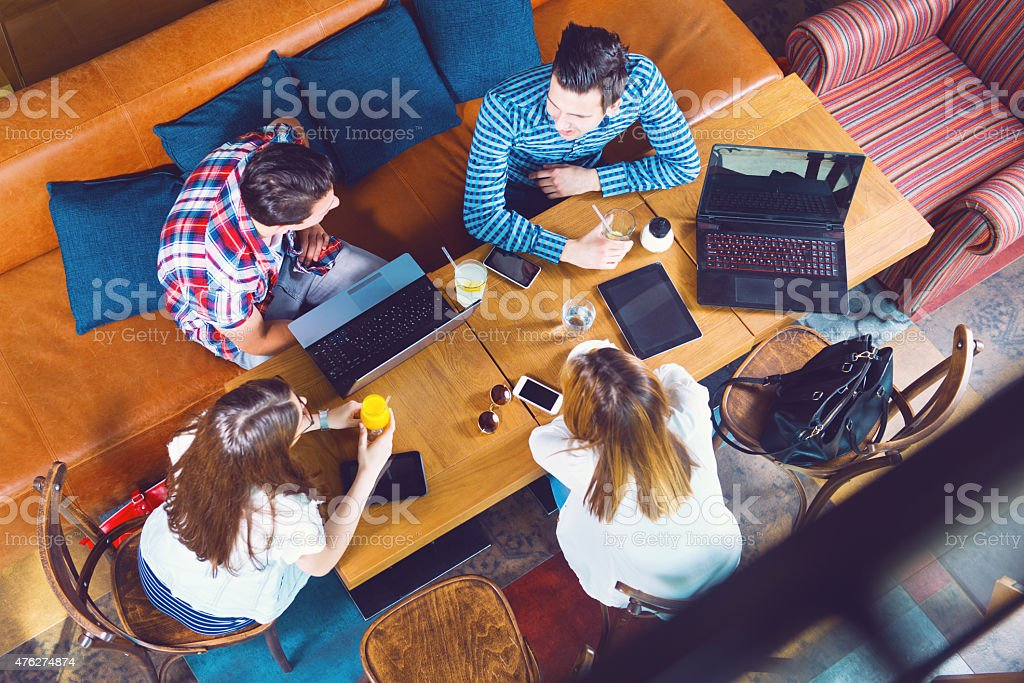 Group of young people sitting at a cafe, top view stock photo