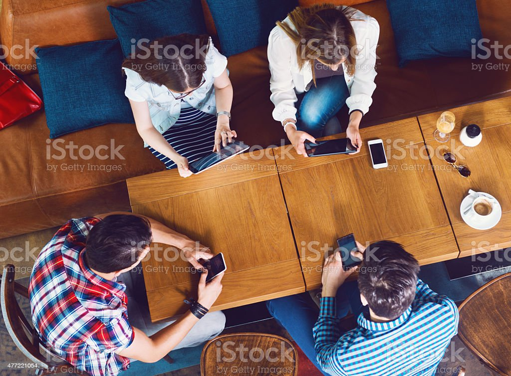 Group of young people sitting at a cafe, top view Group of young people sitting at a cafe, with mobiles and tablets, top view 2015 Stock Photo