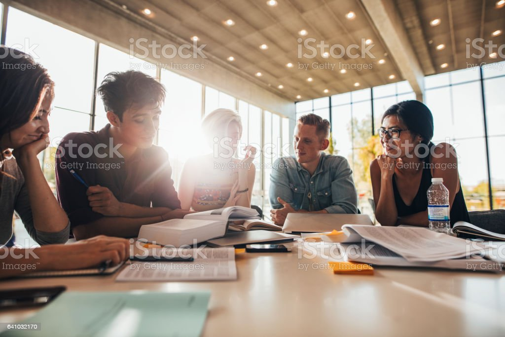 Group of young people sitting at table reading books stock photo