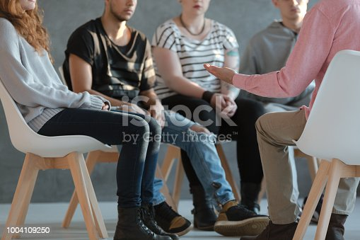 istock Group of young people sitting in a circle and talking to psychiatrist  during a therapy 1004109250