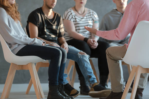 Group of young people sitting in a circle and talking to psychiatrist  during a therapy Group of young people sitting in a circle and talking to psychiatrist  during a therapy counseling stock pictures, royalty-free photos & images