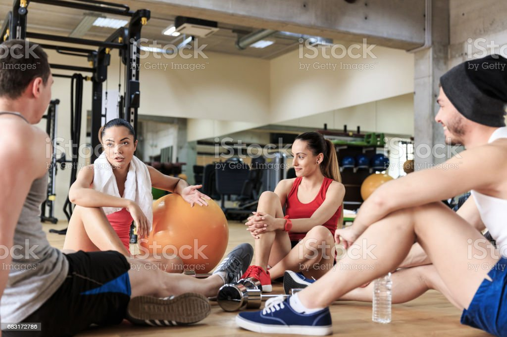 Group of young people sitting on floor in gym royalty-free stock photo