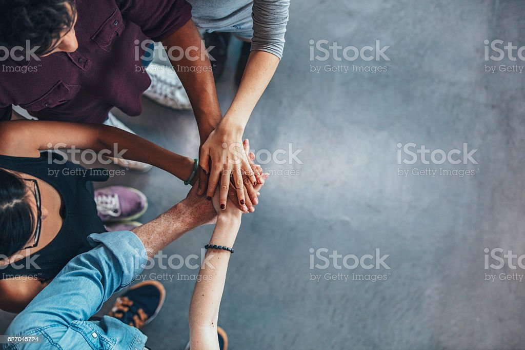 Group Of young people stacking their hands stock photo