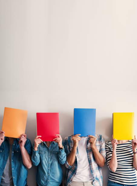 groep jongeren permanent en leunend tegen de muur, houd van kleurrijke mappen voorkant van hun hoofd. - netherlands map stockfoto's en -beelden