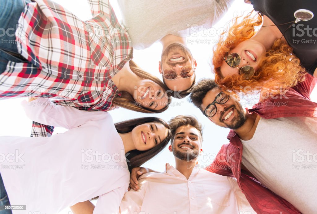 Group of young people standing in a circle, outdoors, having fun royalty-free stock photo