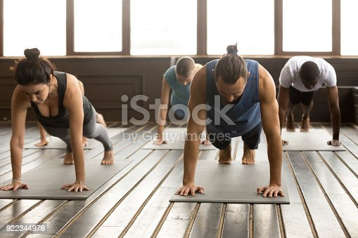 944619806 istock photo Group of young people standing in Plank pose 922344976