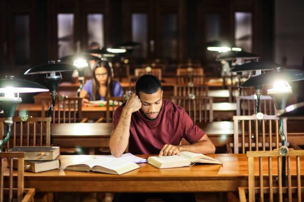 Gruppe junger Leute, die nachts in der Bibliothek studieren – Foto