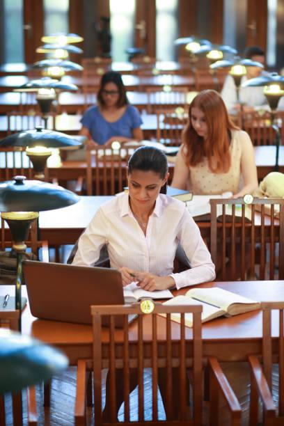 Gruppe junger Menschen, die in der Bibliothek studieren – Foto