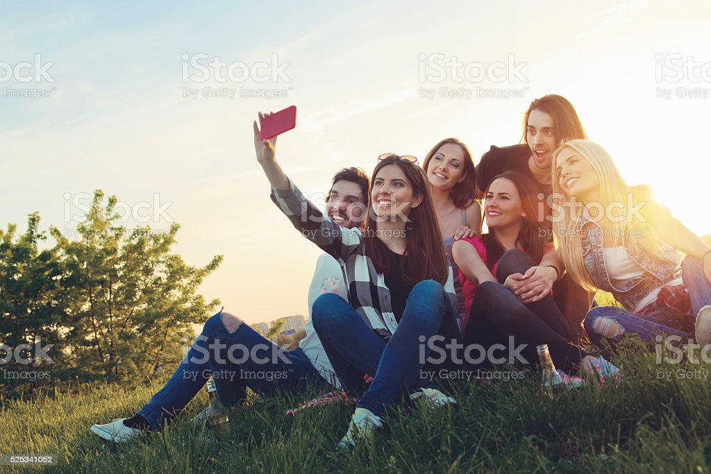 Group of young people taking a selfie outdoors, having fun royalty-free stock photo