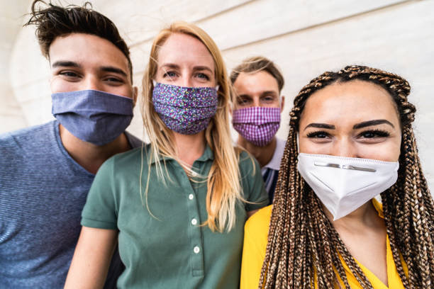 Group of young people taking selfie with phone camera while wearing protective masks - Happy friends taking photos during coronavirus outbreak - Social distancing concept - Focus on right girl eyes stock photo