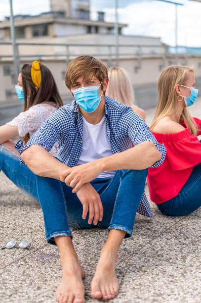 Gruppe von Jugendlichen mit Gesichtsschutzmasken auf dem Boden sitzend – Foto