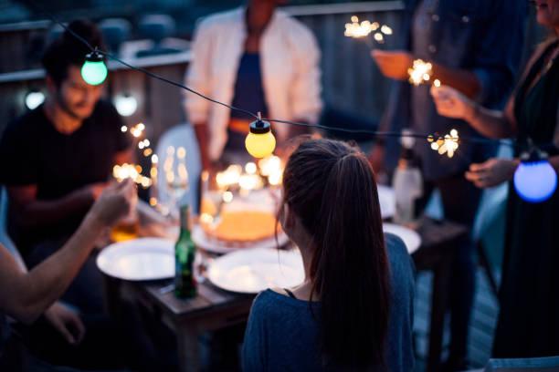 gruppe von jugendlichen mit wunderkerzen auf party auf dem dach - terrassen lichterketten stock-fotos und bilder