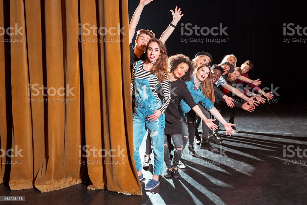 Group of young performers on the stage Group of young performers on the stage standing in the line behind the curtain, raising hands.  20-29 Years Stock Photo