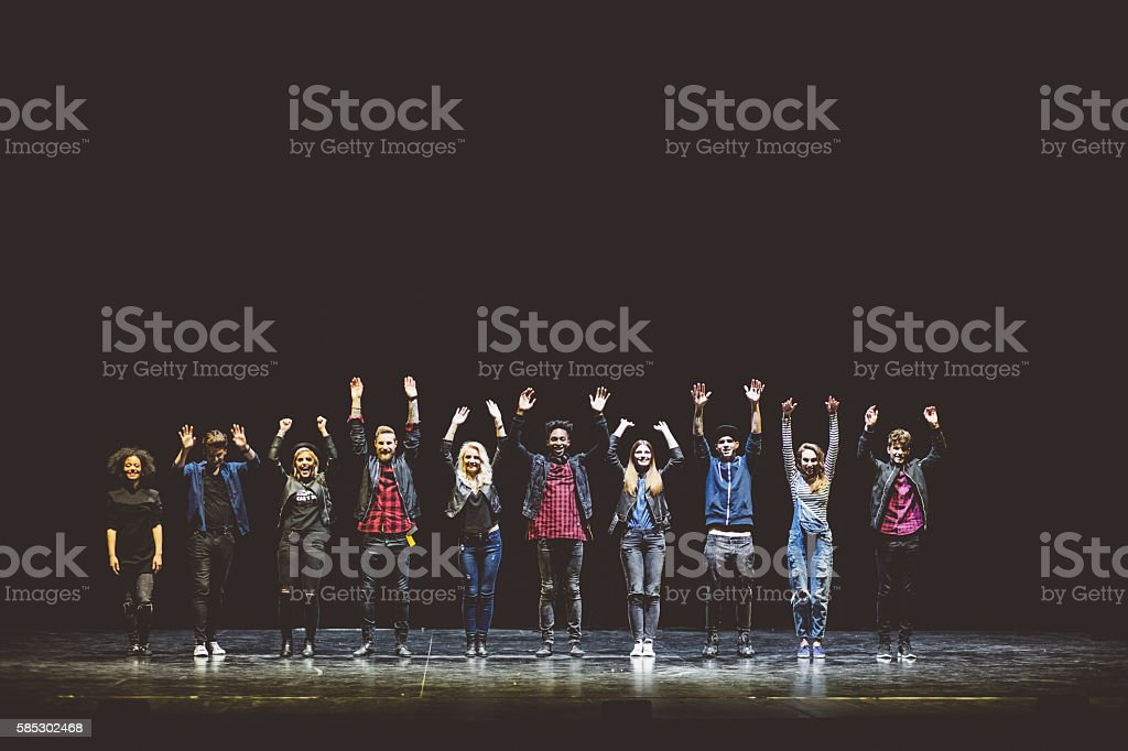 Group of young performers on the stage Group of young performers on the stage standing in the line, raising hands. Dark tones. 20-29 Years Stock Photo