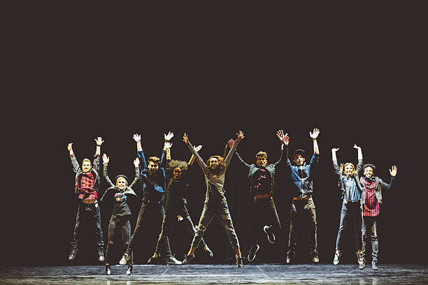 Group of young performers on the stage Group of young performers on the stage standing in the line, jumping with raised hands. Dark tones. performing arts event stock pictures, royalty-free photos & images