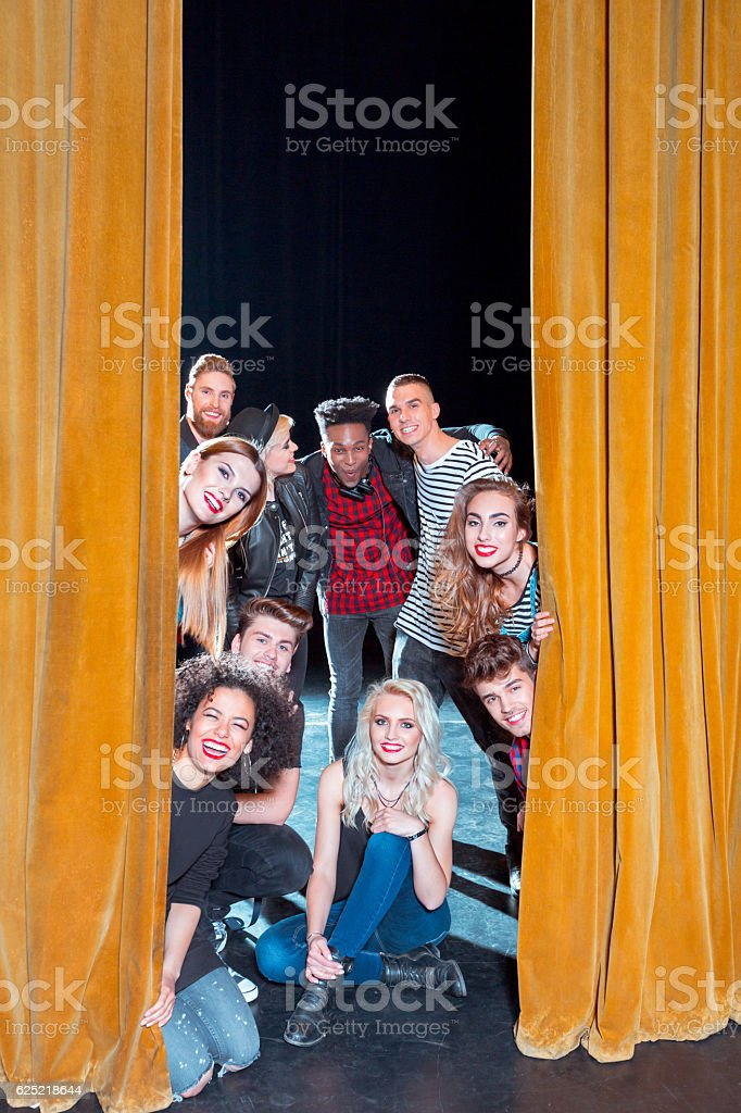 Group of young performers on the stage Group of young performers on the stage standing behind the curtain, smiling at camera. 20-29 Years Stock Photo