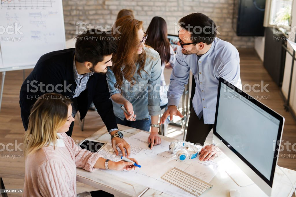 Group of young perspective architects discussing in office royalty-free stock photo
