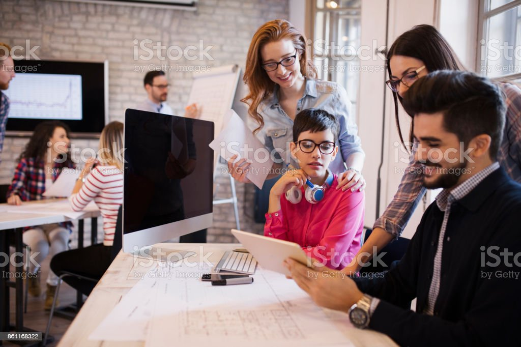 Group of young perspective designers discussing in office royalty-free stock photo