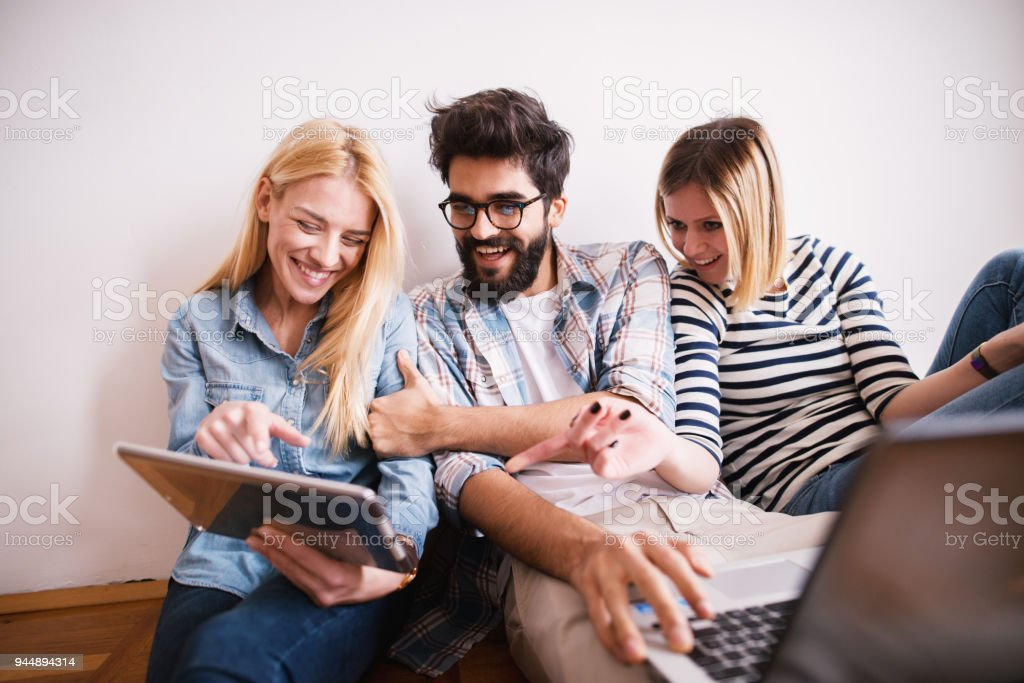 Group of young playful coworkers laughing on internet content from a tablet while sitting on the floor leaning against the wall. stock photo