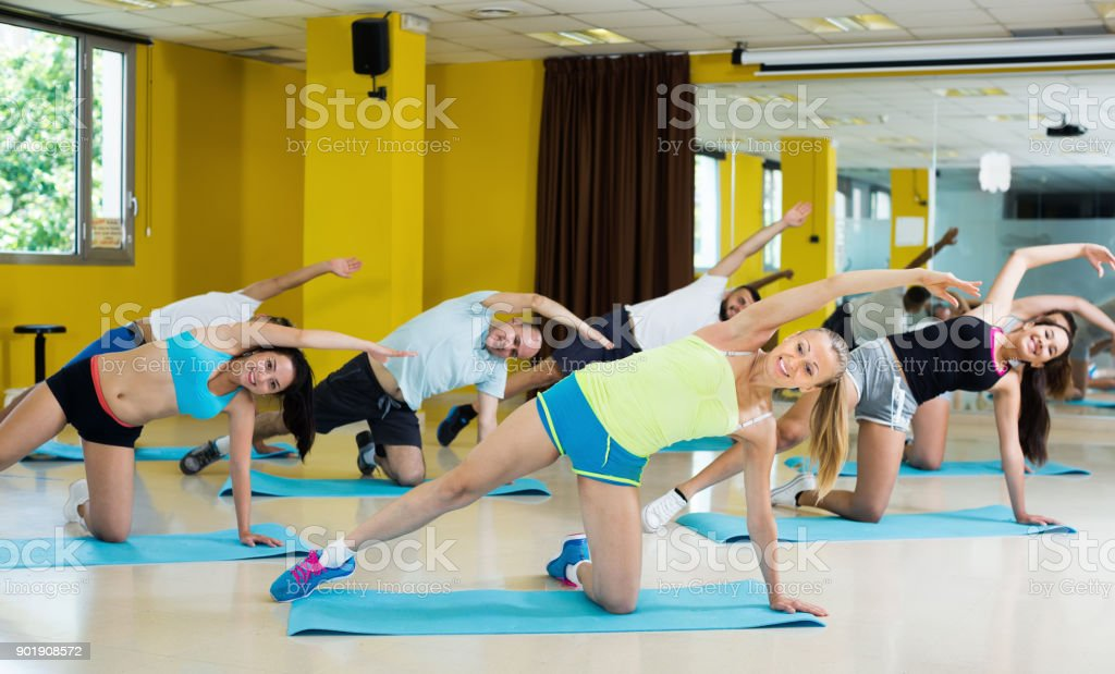 Group of young smiling people exercising stretching in dance hall