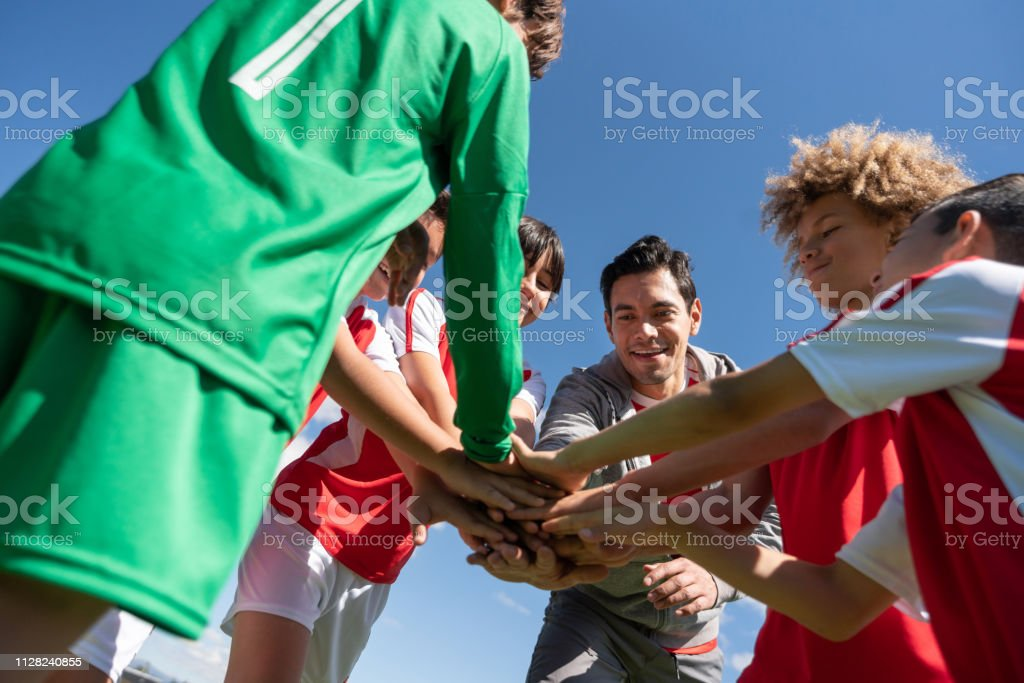 Group of young soccer players having a pep talk with their coach and...