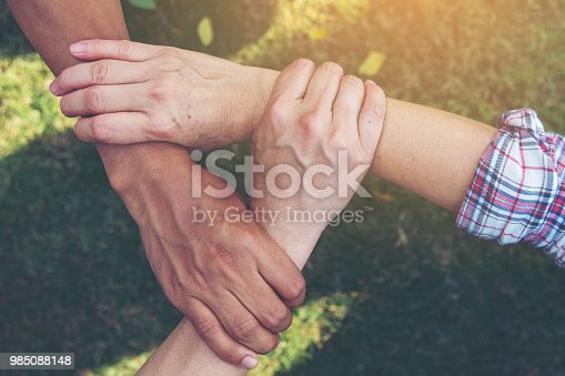 Group of young sport team hands together, team partners giving fist bump come together for sport battle outdoor. Corporate teamwork partnership. Meeting,business concept,vintage tone.