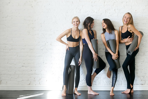 istock Group of young sporty girls with yoga mats, copyspace 914755598