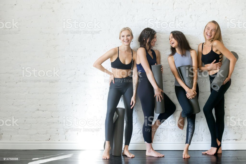 Group of young sporty girls with yoga mats, copyspace stock photo