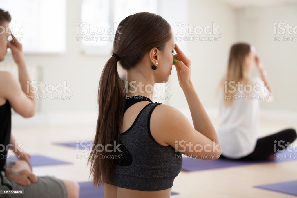 Group of young sporty people doing Alternate Nostril Breathing exercise stock photo