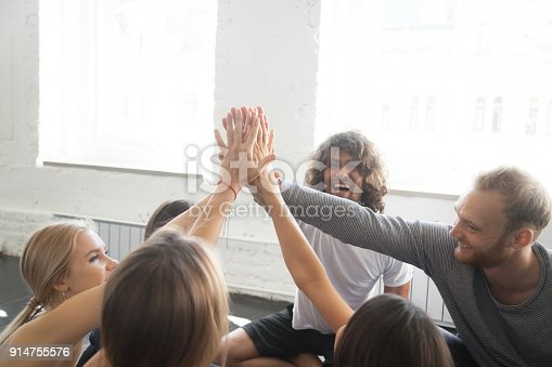 istock Group of young sporty people giving a high five 914755576