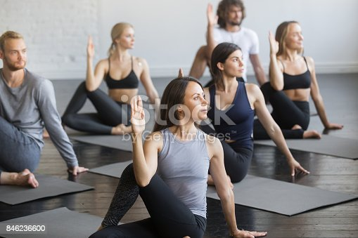 istock Group of young sporty people in Ardha Matsyendrasana pose 846236600