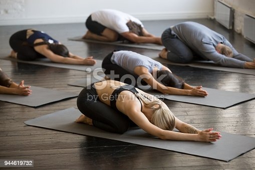 Group of young sporty people practicing yoga lesson, doing Child exercise, Balasana pose, working out, indoor full length, students training in club, studio