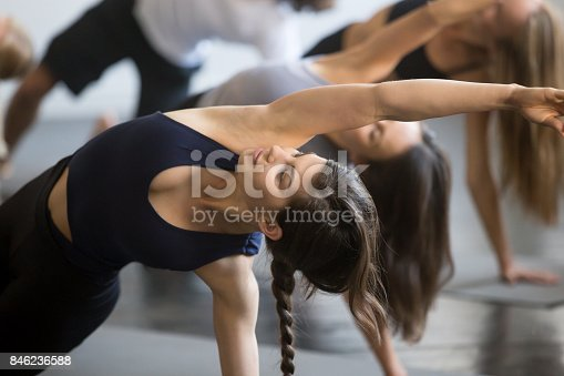 914755448istockphoto Group of young sporty people in Bending Side Plank pose 846236588