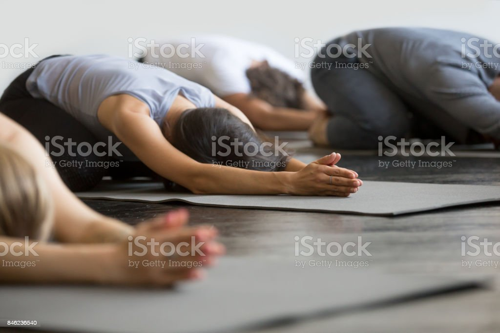 Group of young sporty people in Child pose stock photo