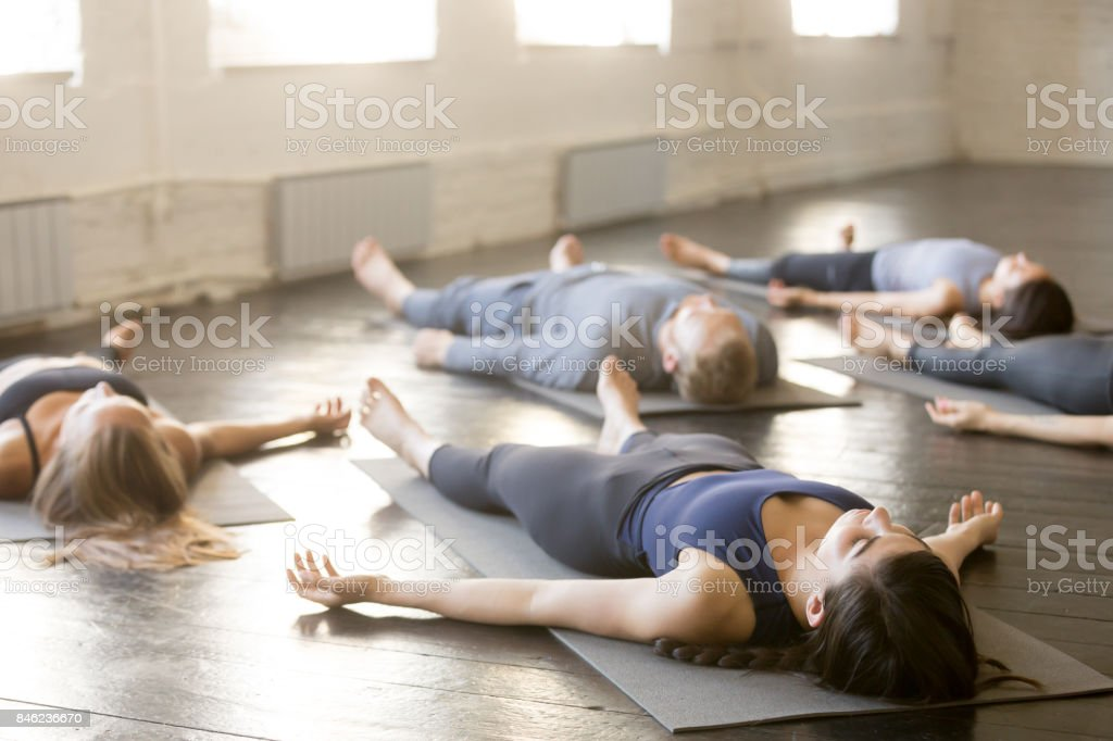 Group of young sporty people in Corpse exercise stock photo