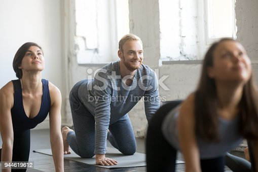 944619806 istock photo Group of young sporty people in Cow exercise 944619612