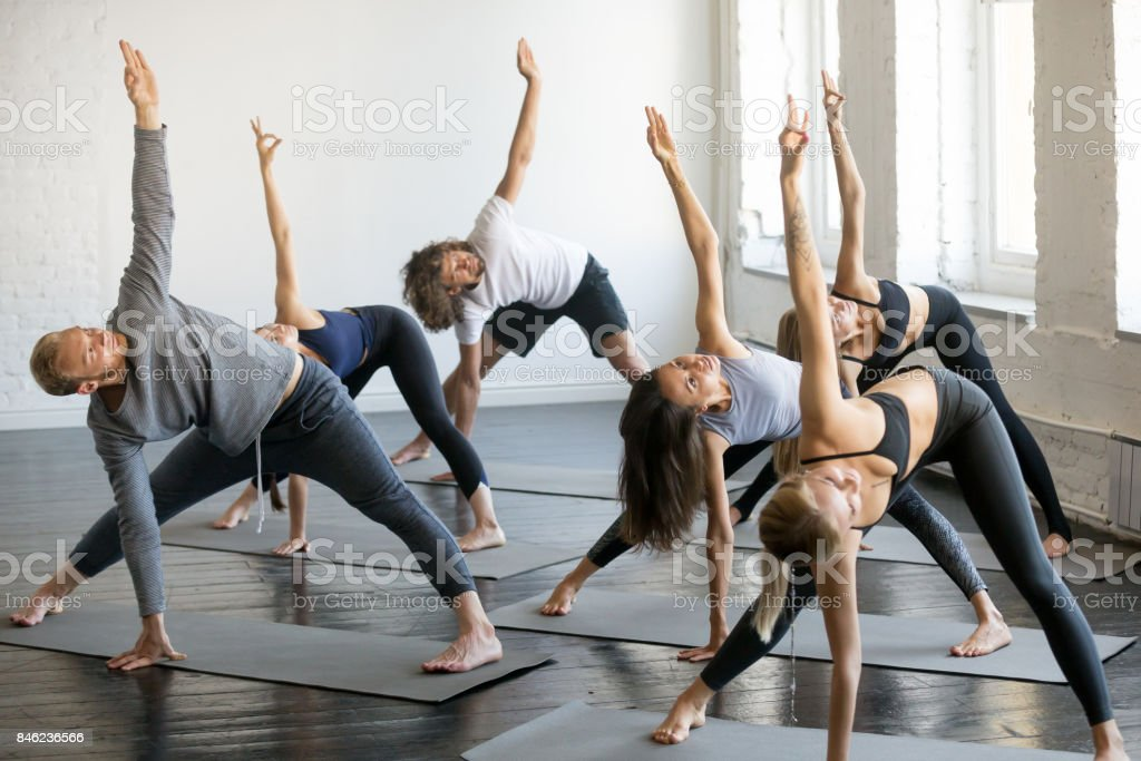 Group of young sporty people in extended triangle pose stock photo