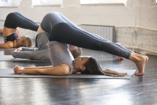 gruppe von jungen sportlichen menschen in halasana-pose - yin yoga stock-fotos und bilder