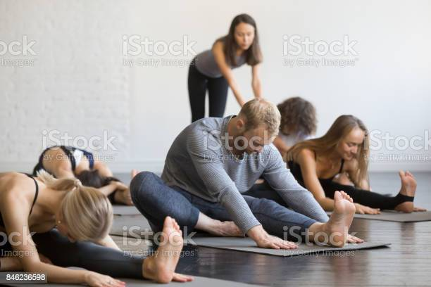 Group of young sporty people in head to knee forward bend pose picture id846236598?b=1&k=6&m=846236598&s=612x612&h=7ohkkwlopqr4 2f5hwokl8jcenddv4qn 2whhytepd0=