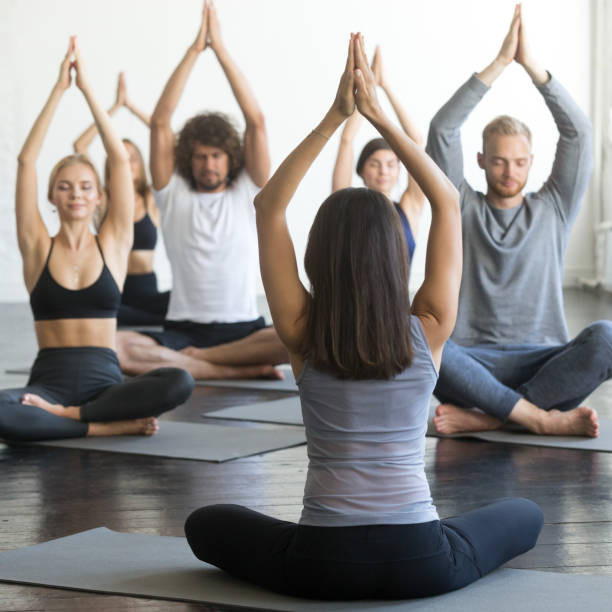 Group of young sporty people in Lotus pose with mudra stock photo