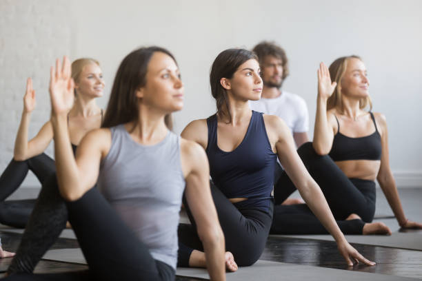 Group of young sporty people in Matsyendrasana pose, close up stock photo