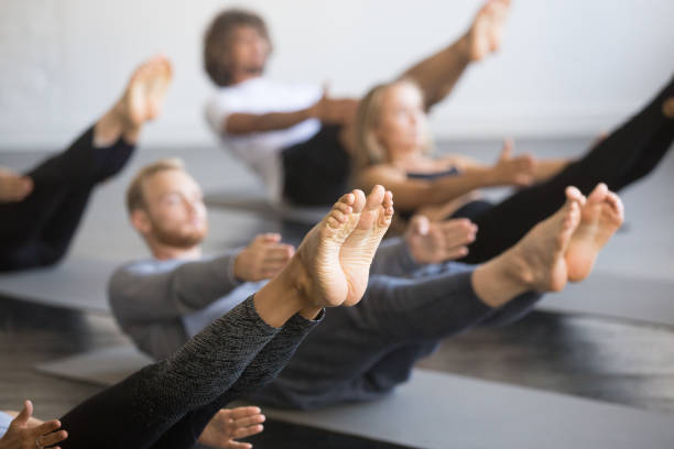 Group of young sporty people in Paripurna Navasana pose stock photo