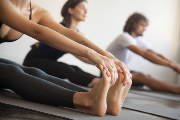 gruppe der jungen sportler in paschimottanasana übung, nahaufnahme - yin yoga stock-fotos und bilder