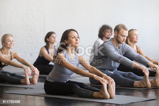 istock Group of young sporty people in paschimottanasana pose 914755498
