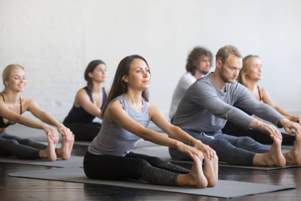 gruppe der sportlichen jugendlichen in paschimottanasana pose - yin yoga stock-fotos und bilder