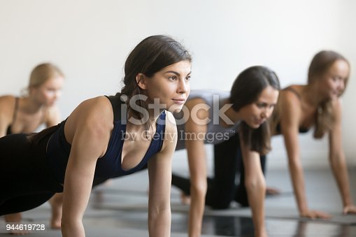 914755448istockphoto Group of young sporty people in Plank pose, close up 944619728